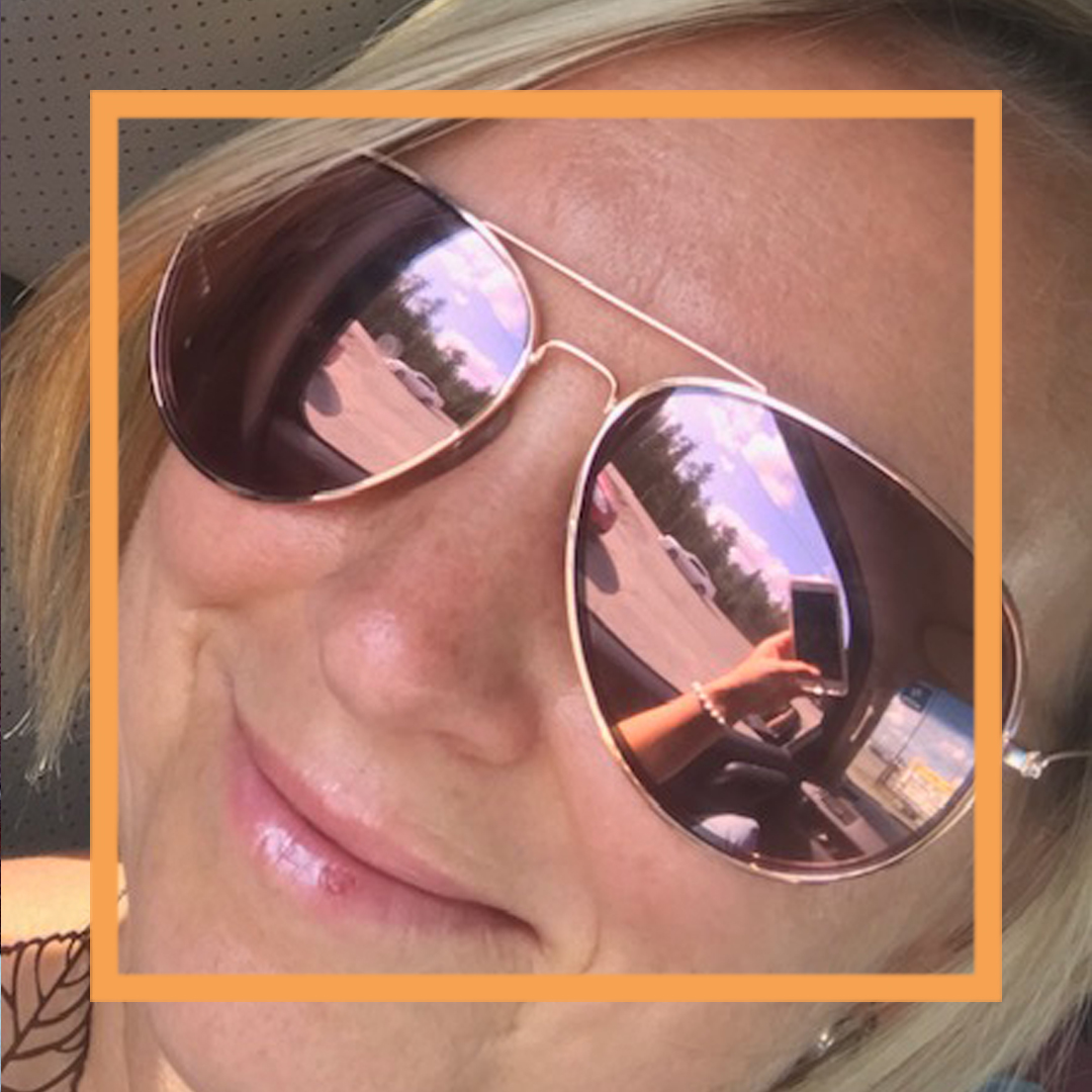 A closeup up of Chrystal smiling at the camera and wearing aviator sunglasses. There is a thin orange box framing the photo.