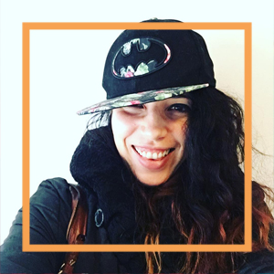 Nicole wears a flatbrimmed black cap with the batman logo and smiles at the camera