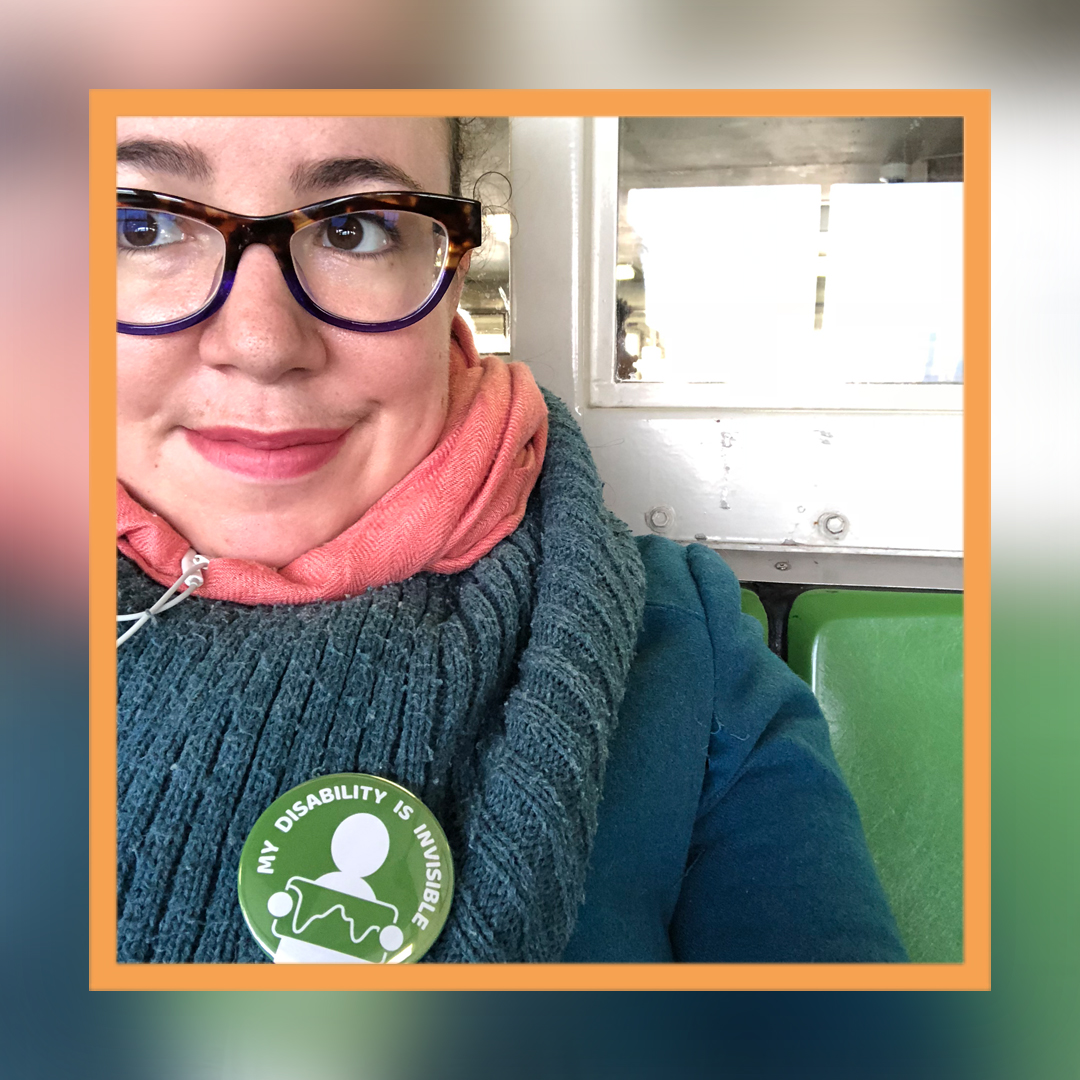 "A close-cropped photo of Tema's face and shoulders. She is wearing tortoise shell glasses and looking off camera, and wearing a thick wool scarf with a green button that reads ""My disability is invisible."""
