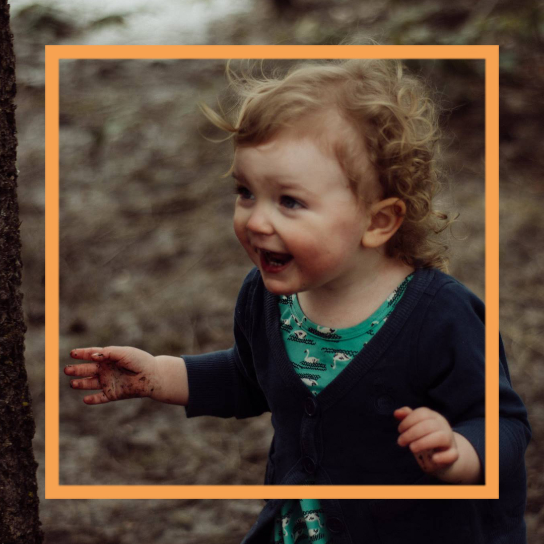 A photo of India, a 2-year-old girl, standing in the woods and smiling off camera.