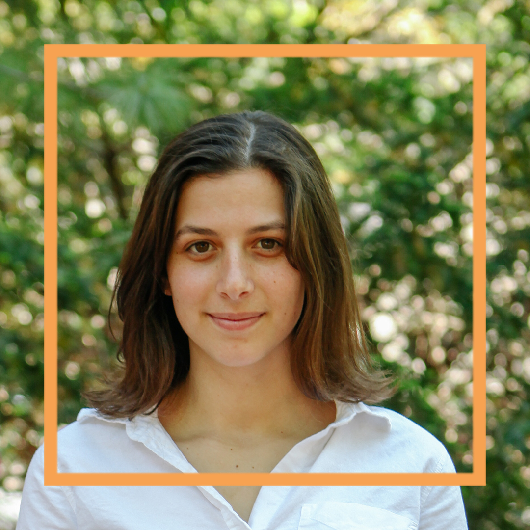 Hannah is wearing a white button-up shirt and standing in front of blurry greenery. She is looking directly at the camera and smiling. There is an orange box superimposed over the photo.