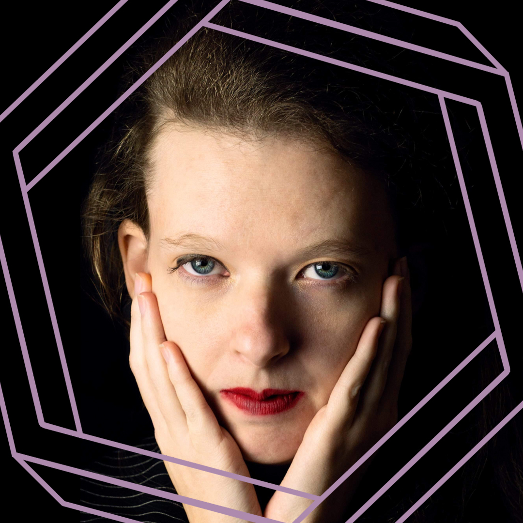 Belle is wearing bright red lipstick and looking at the camera while she rests her chin on her hands. There is a stylized purple hexagon superimposed around her face.