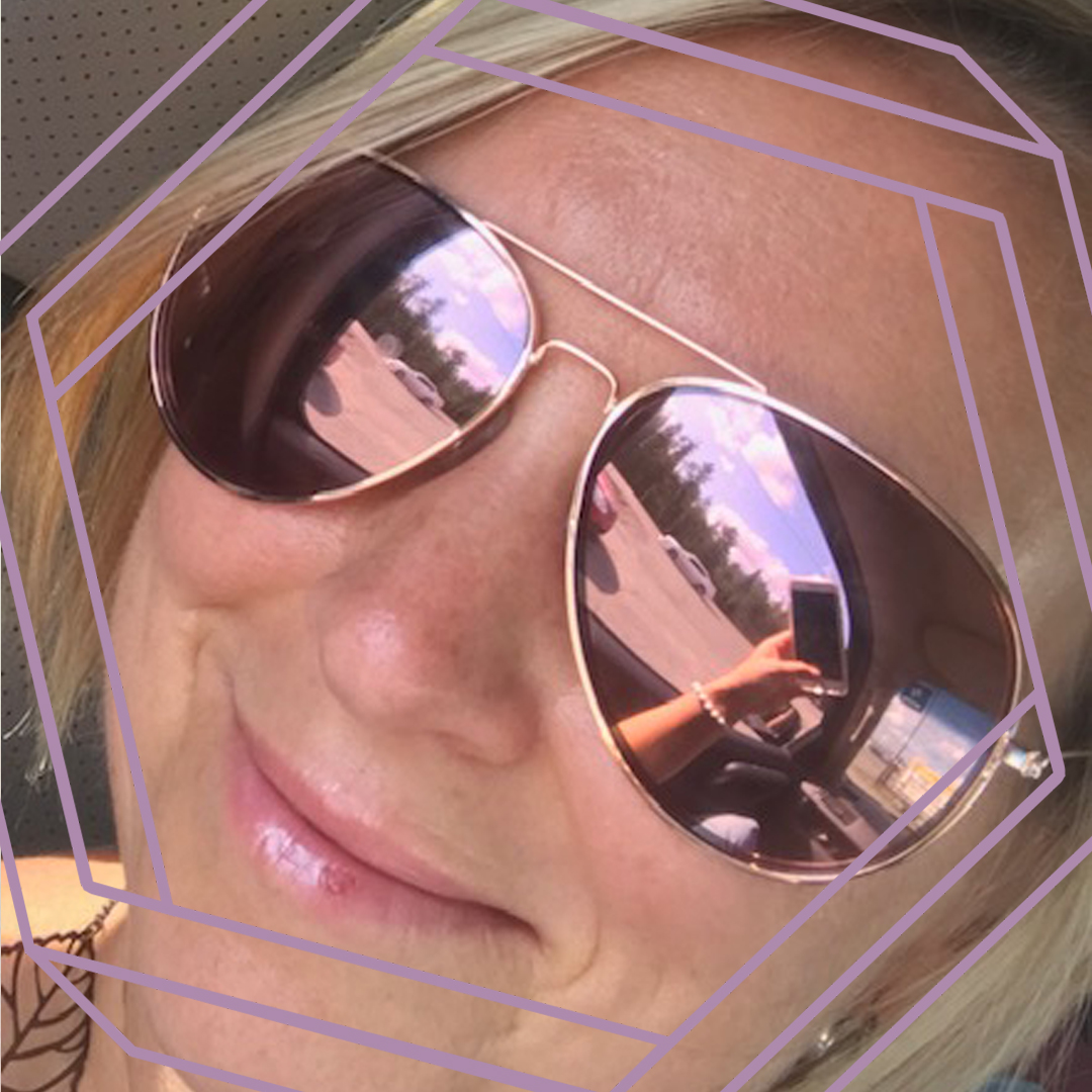 A closeup up of Chrystal smiling at the camera and wearing aviator sunglasses. There is a stylized purple hexagon framing the photo.