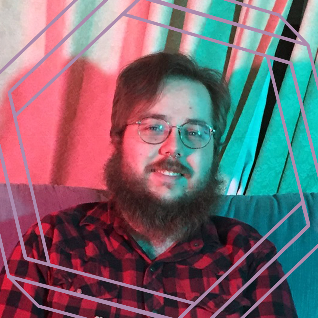 David, a white man with glasses and a beard, smiles at the camera. There is a stylized purple hexagon framing the photo.