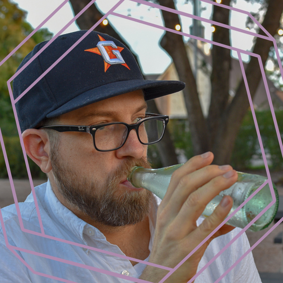 Garreth, a man with a beard, black framed glasses and a navy blue baseball cap, is drinking from a glass bottle and looking off camera. There is a stylized purple octagon superimposed over the photo.