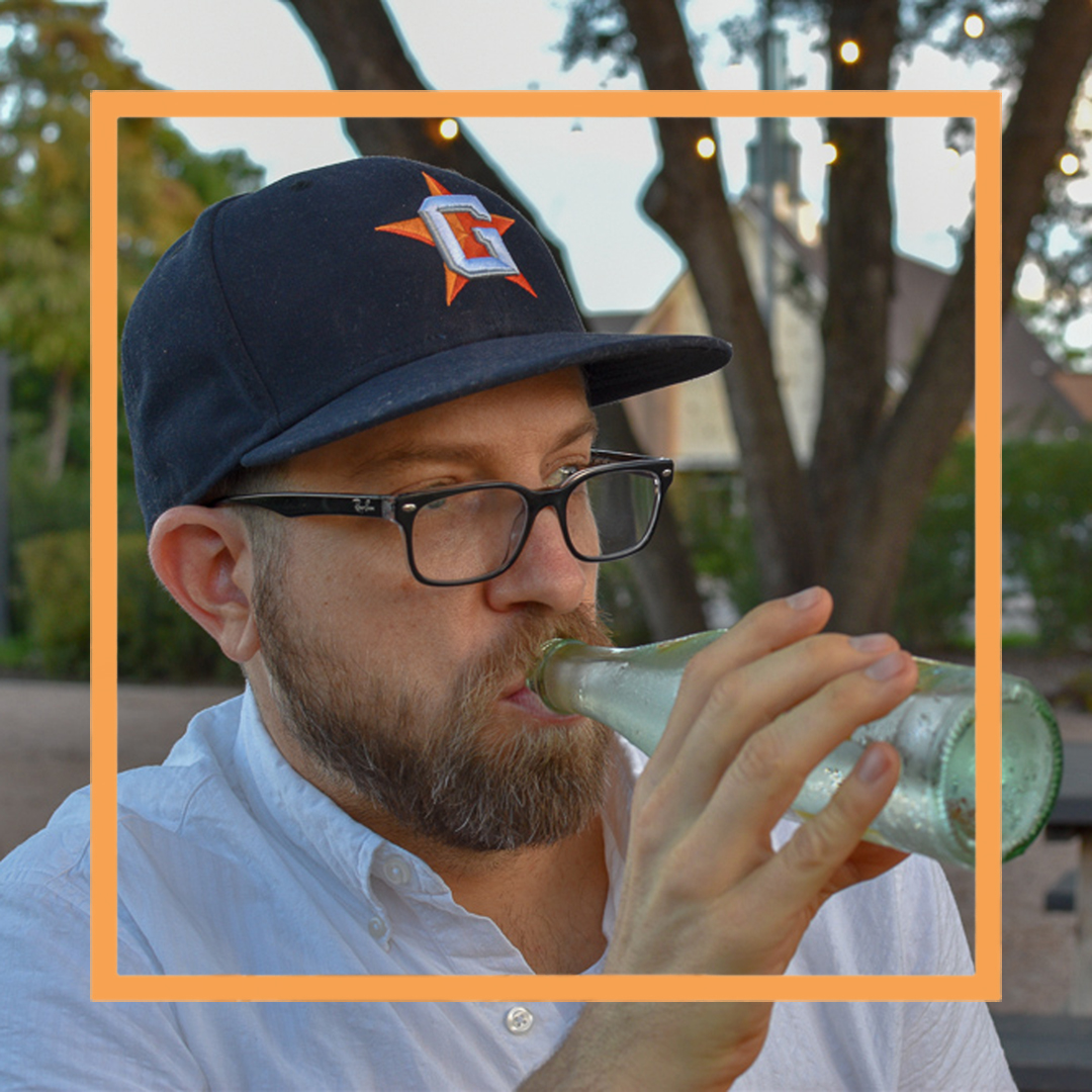 Garreth, a man with a beard, black framed glasses and a navy blue baseball cap, is drinking from a glass bottle and looking off camera. There is an orange square superimposed over the photo.