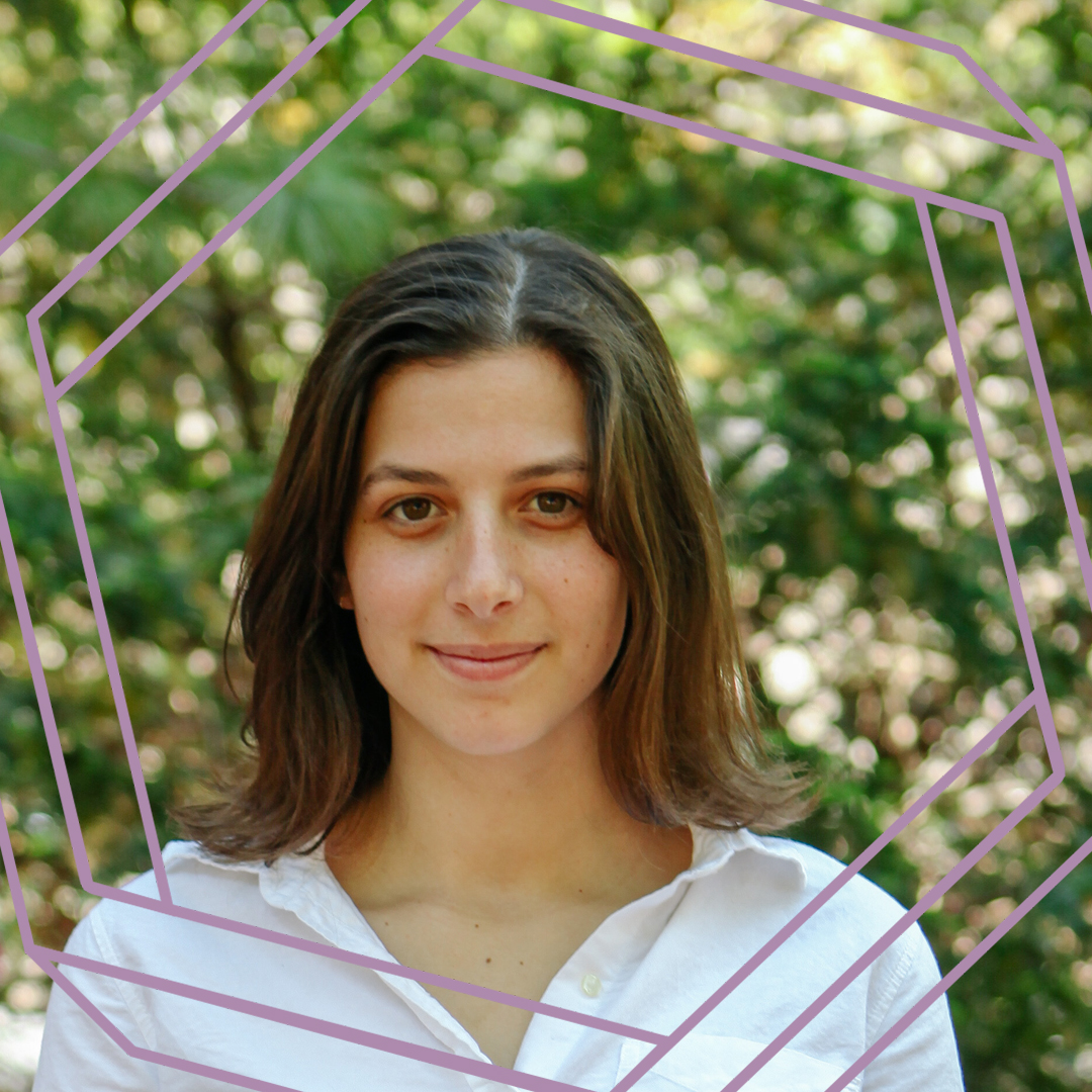 Hannah is wearing a white button-up shirt and standing in front of blurry greenery. She is looking directly at the camera and smiling. There is a stylized purple octagon superimposed over the photo.