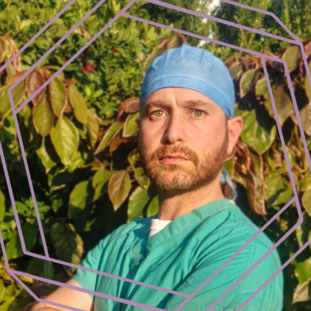 Jacob is standing in front of a shrub, wearing medical scrubs and looking at the camera. There is a stylized purple hexagon superimposed over the photo.