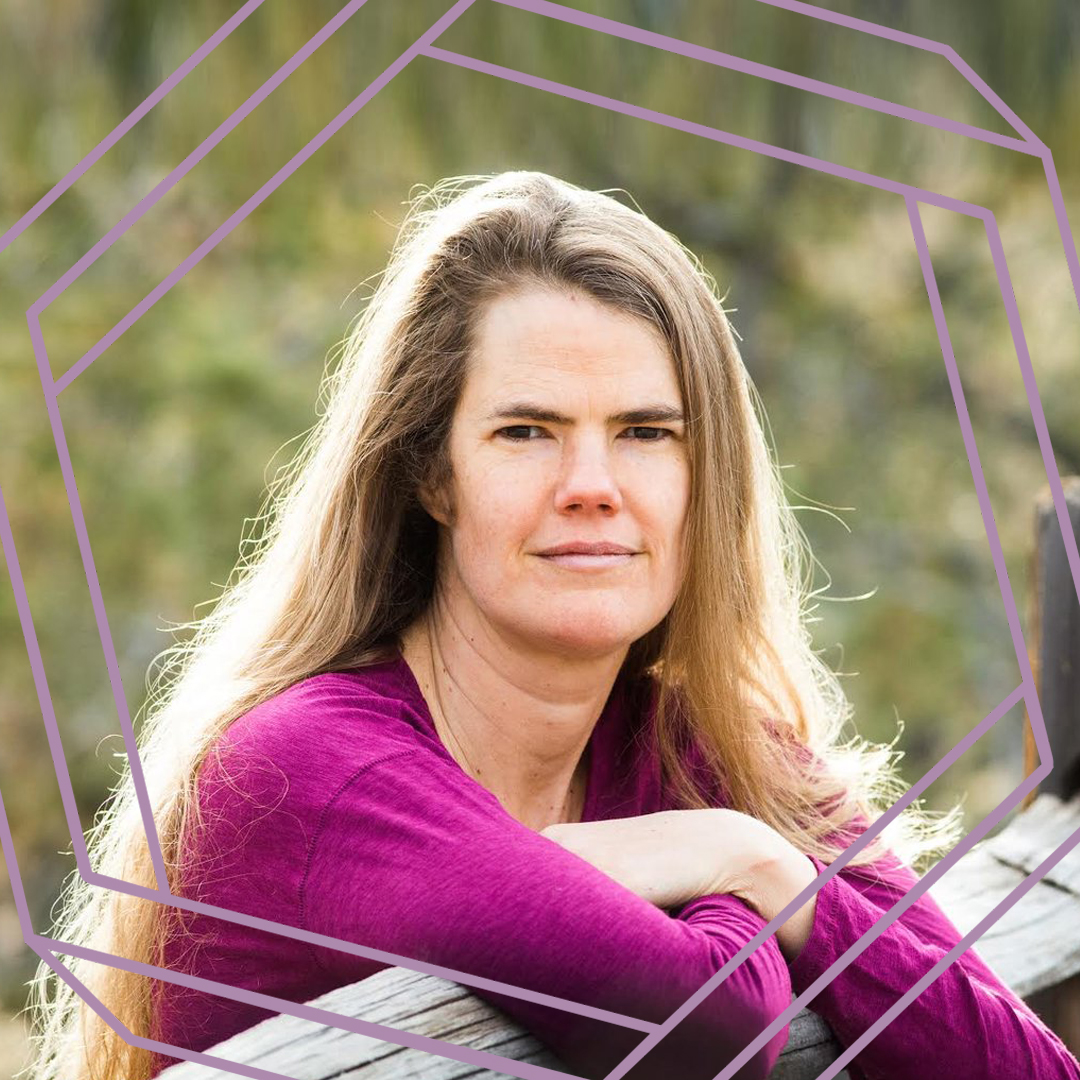 Julie is wearing a magenta sweater and leaning on a split rail fence. She is standing in the sun and looking straight at the camera. There is a stylized purple octagon superimposed over the photo.
