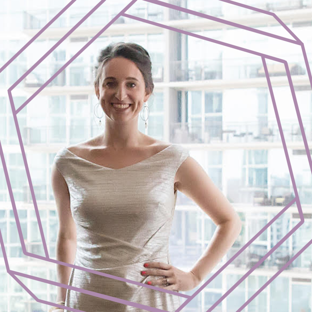 Kelly, a white woman wearing a white dress, smiles at the camera. There is a stylized purple hexagon framing the photo.