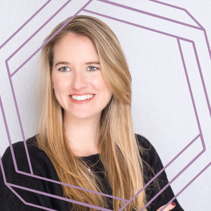 Liz, a white woman with long blonde hair, smiles and looks slightly off camera. There is a stylized purple hexagon framing the photo.