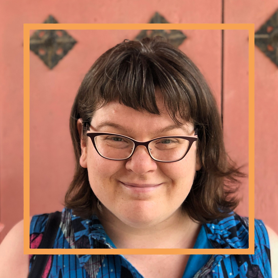 Meredith, a white woman with shoulder-length brown hair and black framed glasses, smiles at the camera. There is an orange square superimposed over her face.