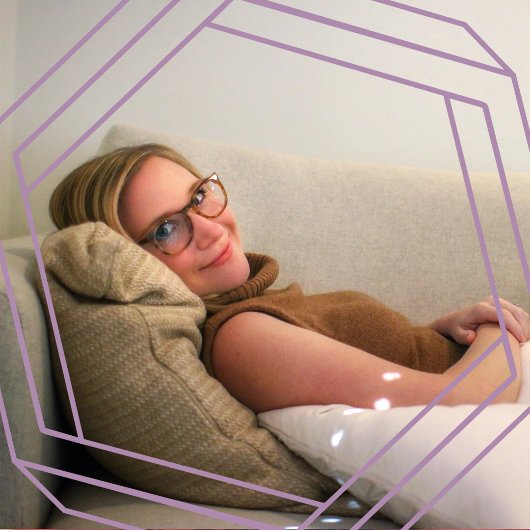 a photo of Natasha reclined on the couch, smiling at the camera. There is a stylized purple hexagon framing the photo.