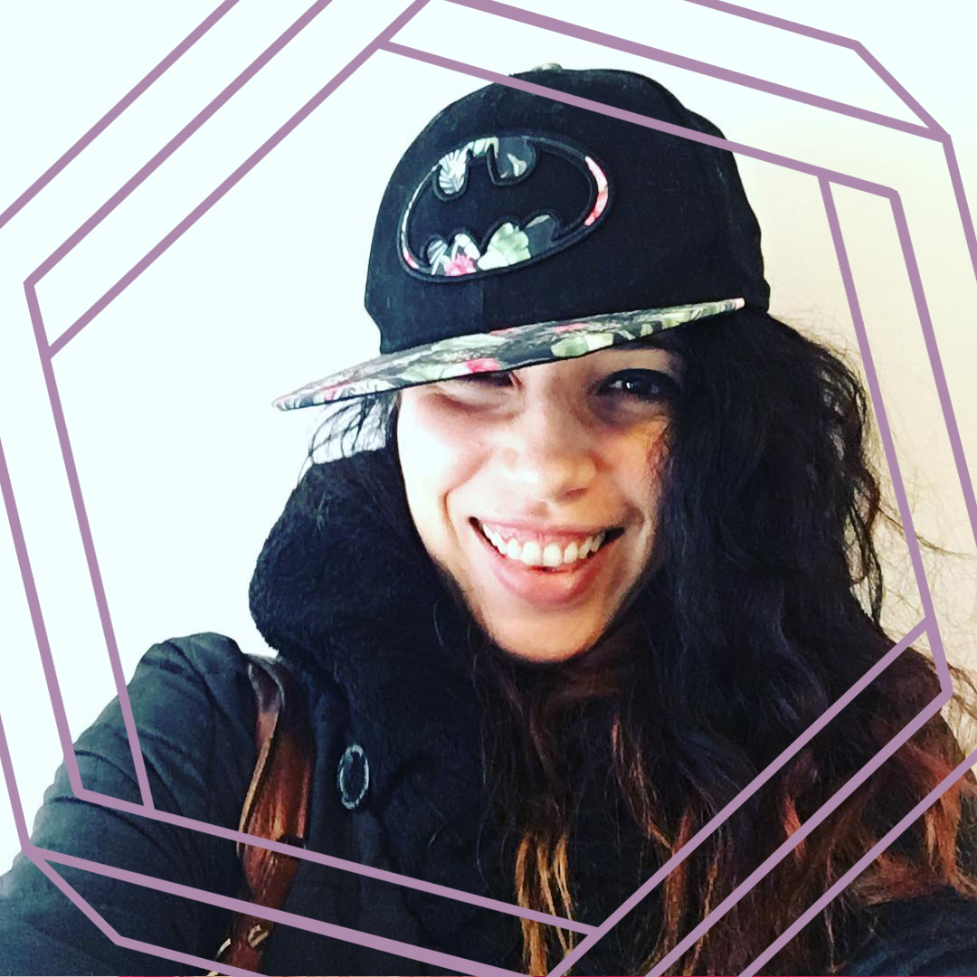 Nicole wears a flatbrimmed black cap with the batman logo and smiles at the camera. There is a stylized purple hexagon framing the photo.