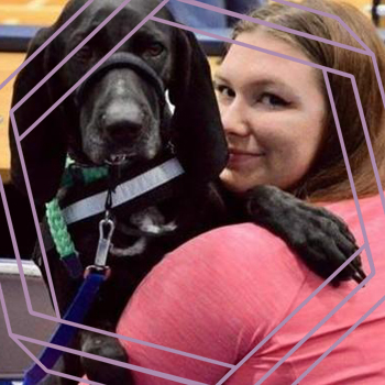 A photo of Rebekah looking over her shoulder and smiling at the camera while her black service dog Zoey rests on her shoulder. There is a stylized purple hexagon framing the photo.