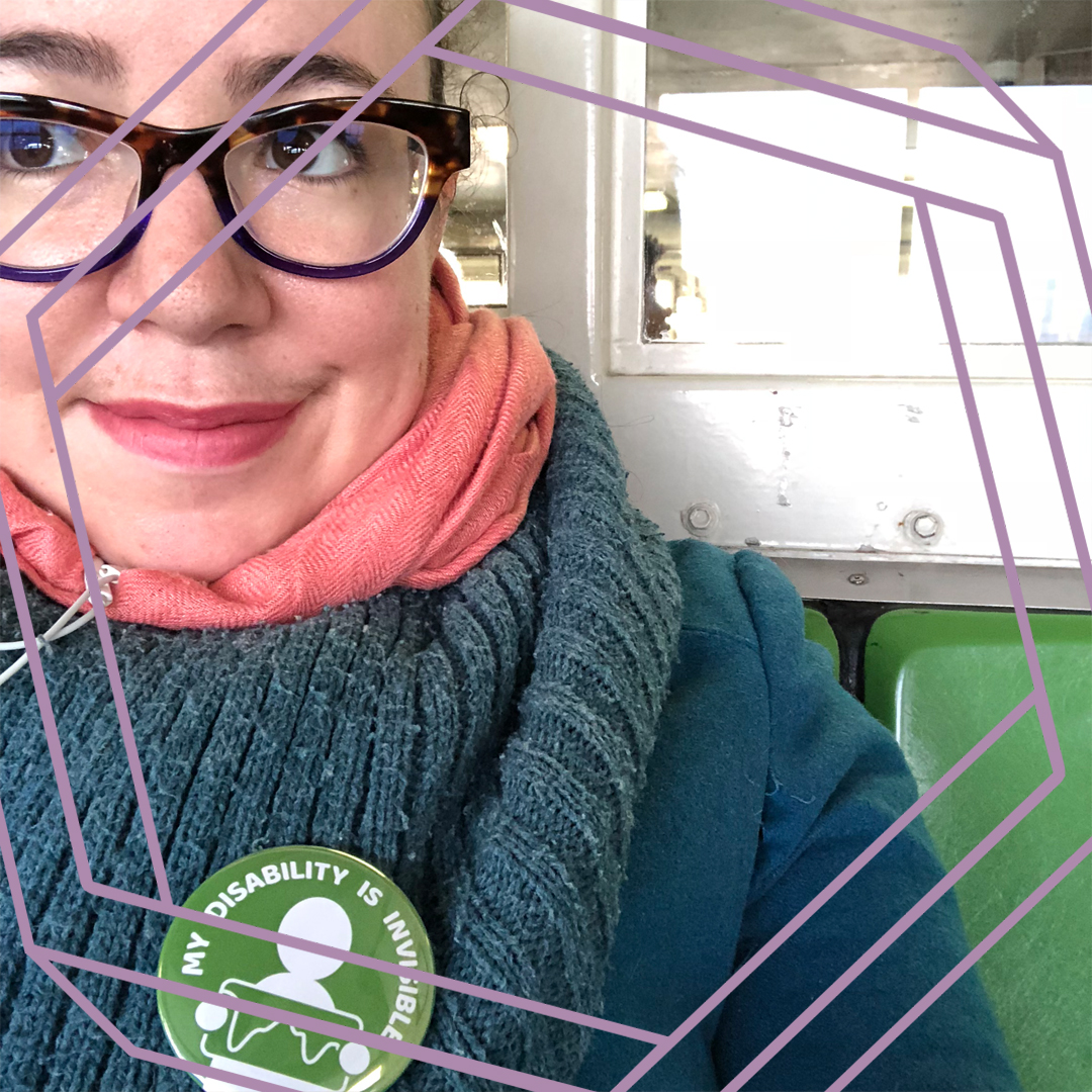 "A close-cropped photo of Tema's face and shoulders. She is wearing tortoise shell glasses and looking off camera, and wearing a thick wool scarf with a green button that reads ""My disability is invisible."" There is a stylized purple hexagon superimposed over the photo."