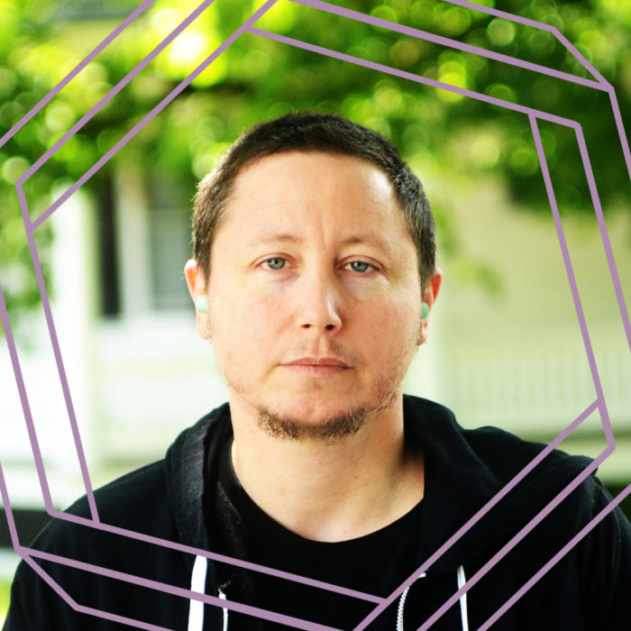Dov, a white man with short dark hair and a goatee, looks directly at the camera. He is wearing a black hoodie and stands in front of a blurry green background. There is a stylized purple octagon superimposed over the photo.