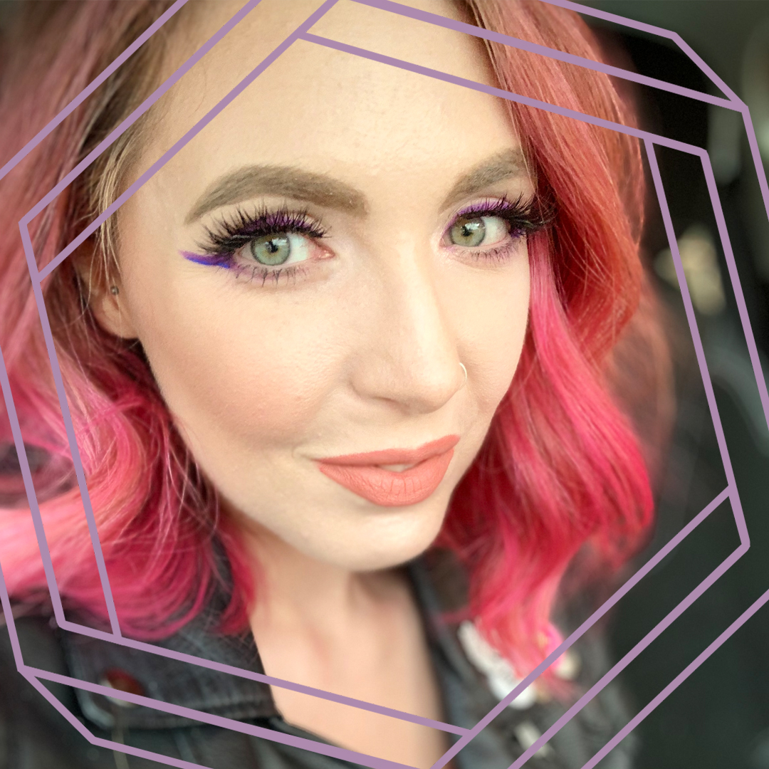 Emma, a white woman with curled pink hair, smiles at the camera. There is a stylized purple octagon superimposed over the photo.