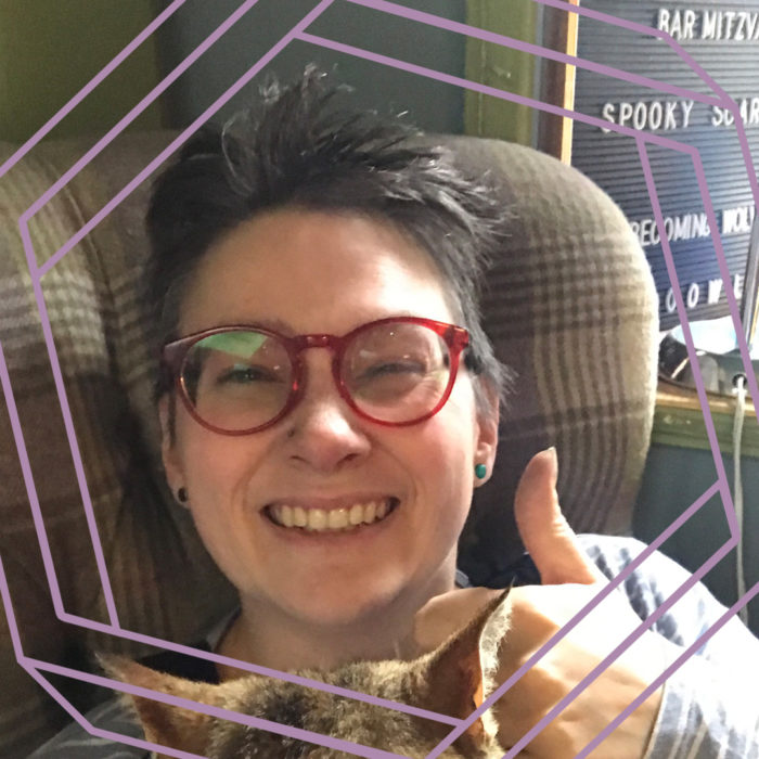 Mairi, a white woman with short dark hair and red framed glasses is smiling at the camera and giving a thumbs up. There is a stylized purple octagon superimposed over the photo.
