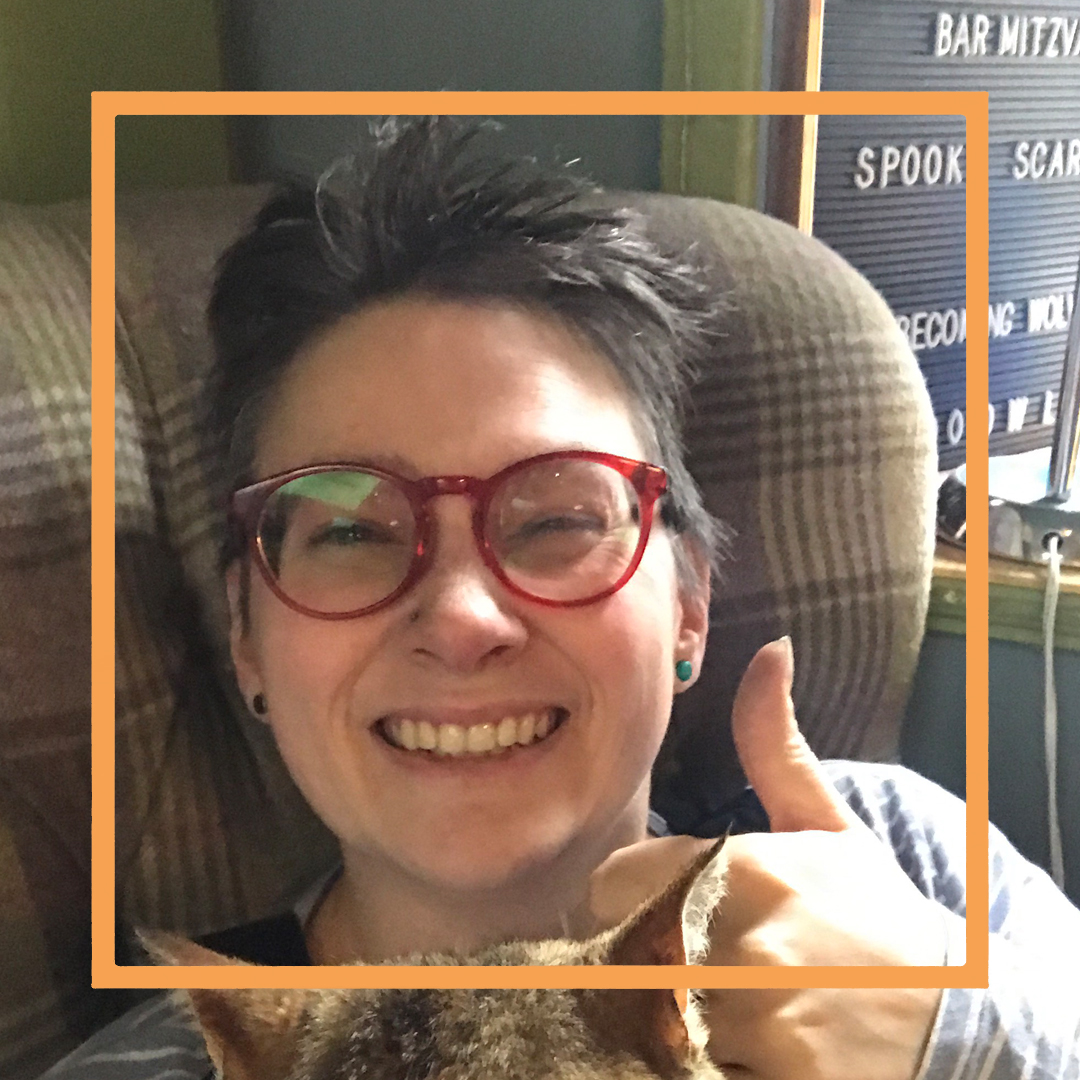 Marie, a whit woman with short dark hair and red framed glasses is smiling at the camera and giving a thumbs up. There is an orange box superimposed over the photo.