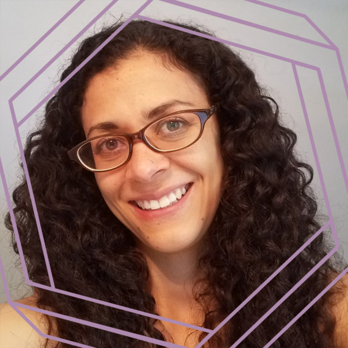 Sara, a woman with long curly brown hair and dark plastic framed glasses, smiles at the camera. There is a stylized purple octagon superimposed over the photo.