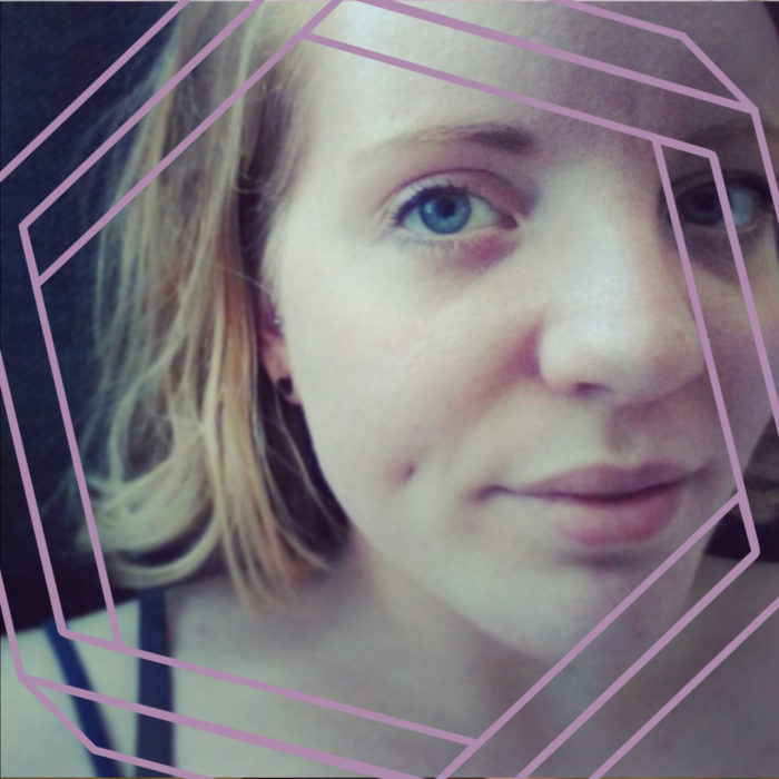 Annie, a white woman with blonde or auburn shoulder-length hair, looks at the camera. The photo is cropped close around her face and framed by a purple hexagon.