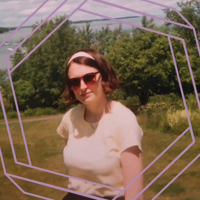 Olivia, a white woman wearing sunglasses, a light headband, and a yellow tshirt, looks at the camera. There is greenery and open water in the background. There is a purple hexagon superimposed over the photo.