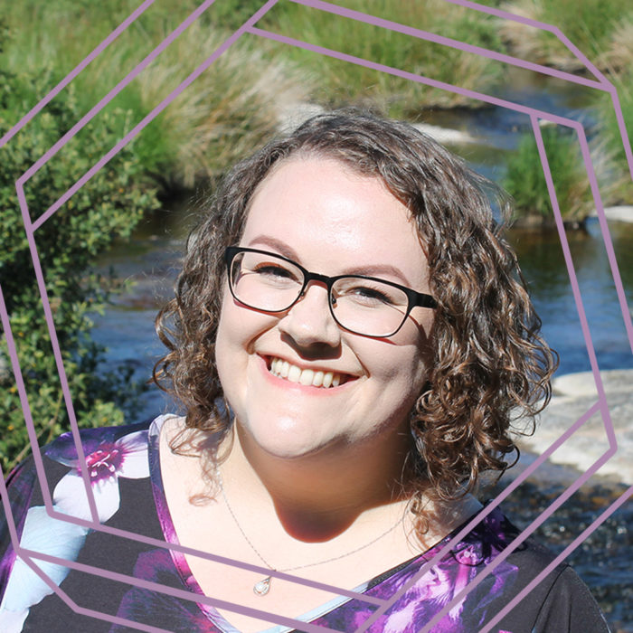 Sarah, a white woman with shoulder-length curly brown hair, smiles at the camera. There is a stream with grassy banks behind her and a stylized purple octagon superimposed over the photo.