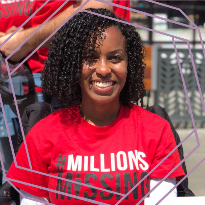 "Ashanti, a black woman with curly shoulder-length black hair, smiles at the camera. She is wearing a red shirt that reads ""#Millions Missing."" There is a purple hexagon superimposed over the photo."