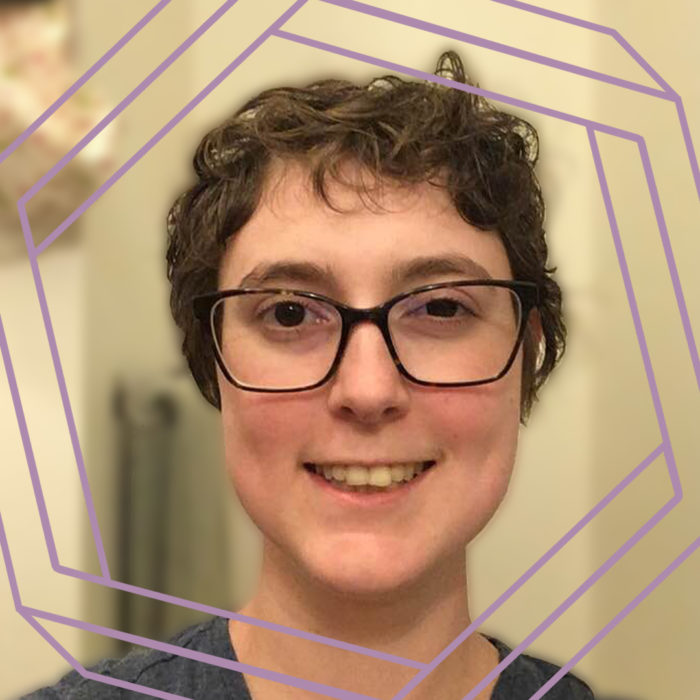 Nora, a white woman with black-framed glasses and short curly brown hair smiles at the camera. There is a stylized purple hexagon framing the photo.