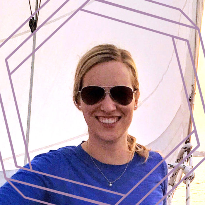 Rachel, a white woman with blonde hair pulled back in a ponytail, wears aviator sunglasses and smiles at the camera. She is wearing a long-sleeved purple shirt and standing in front of a white sail. There is a stylized purple hexagon framing the photo.