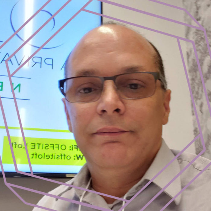 Frank, a man in his 50s wearing glasses, looks at the camera. There is a stylized hexagon framing the photo.