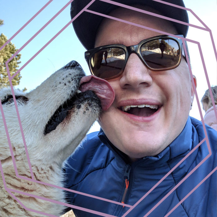 Steve, a white man wearing sunglasses and a ball cap, smiles at the camera while a yellow dog licks his cheek. There is a stylized purple hexagon framing the photo.