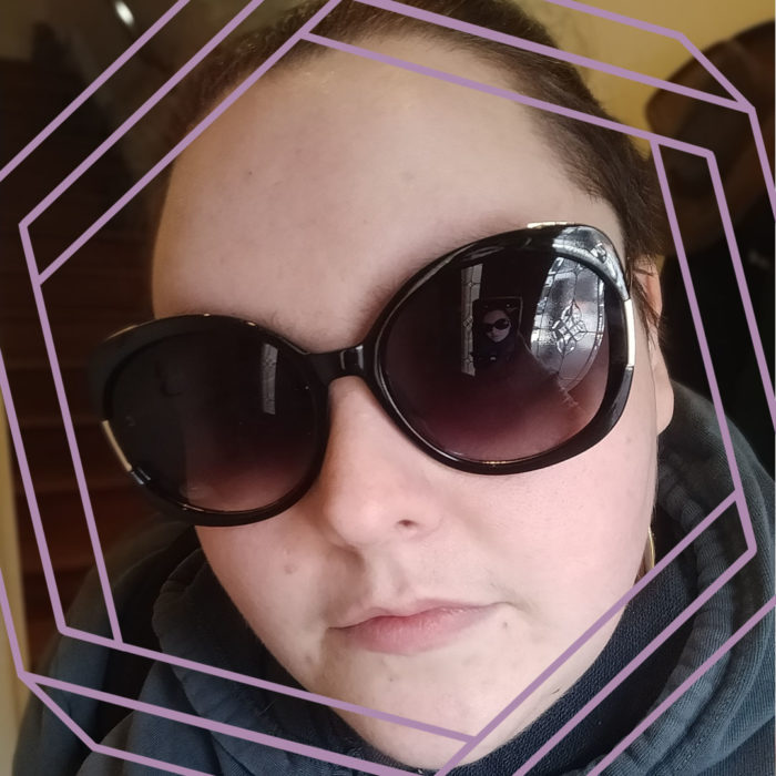 Photo of Emma, a white woman wearing large sunglasses, looking at the camera. There is a stylized hexagon framing the photo.