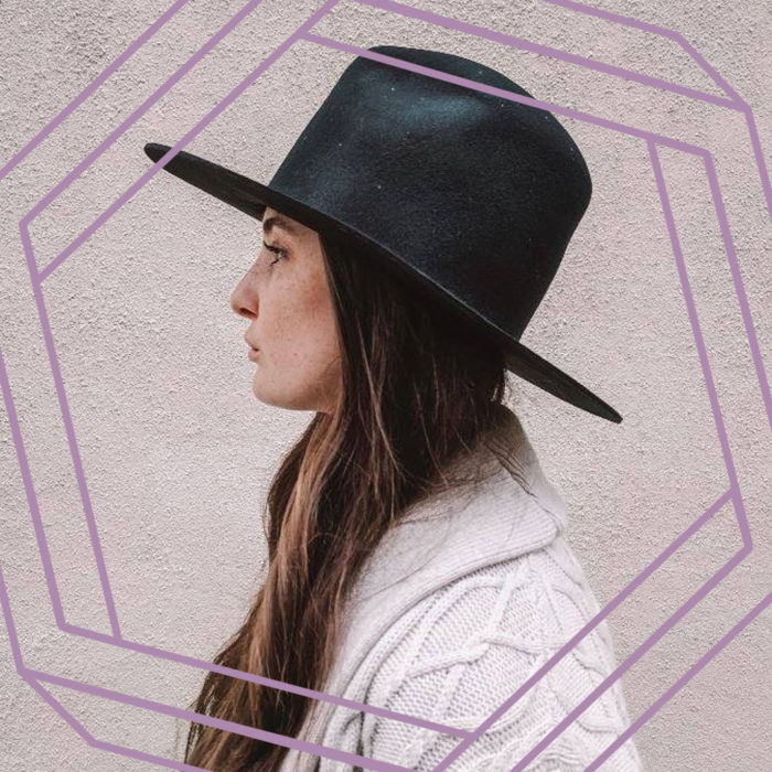 A photo of Taryn in profile.Taryn is a white woman with long brown hair wearing a wide-brimmed black hat and a cable-knit sweater. There is a stylized purple hexagon framing the photo.