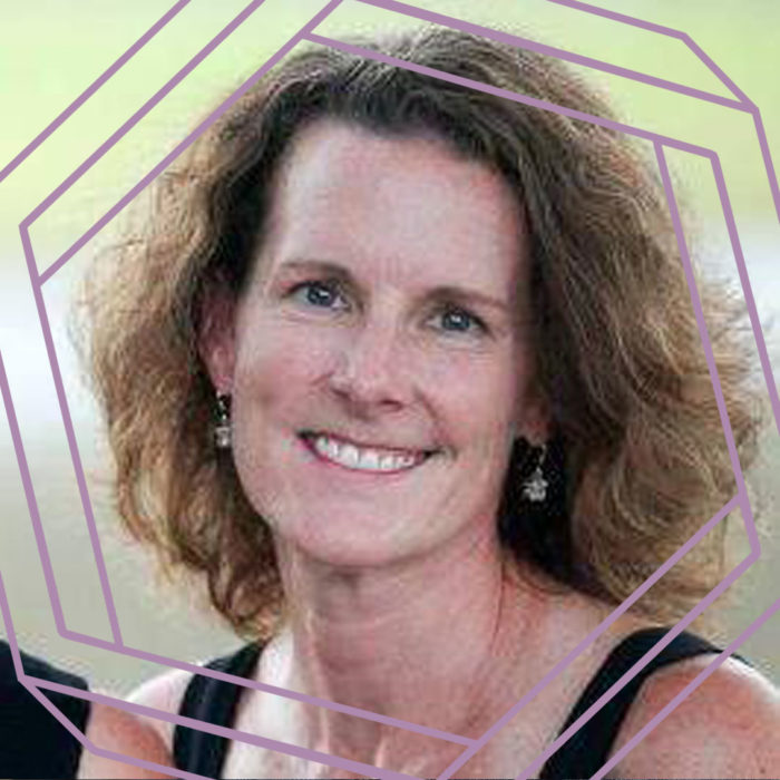 Randee, a white woman in her forties with wavy shoulder-length brown hair, smiles at the camera. There is a stylized purple hexagon framing the photo.