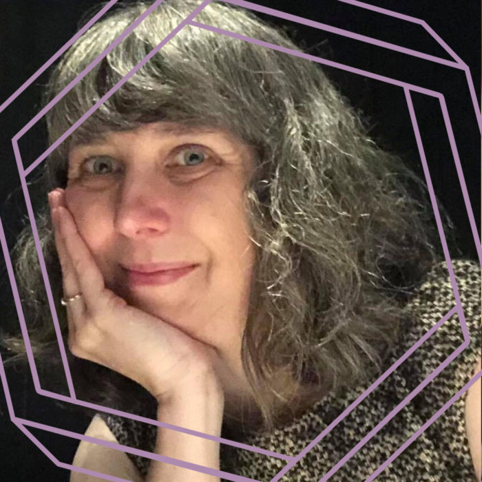 Michelle, a white woman with long grey hair, rests her chin on her hand and smiles at the camera. There is a stylized purple hexagon framing the photo.