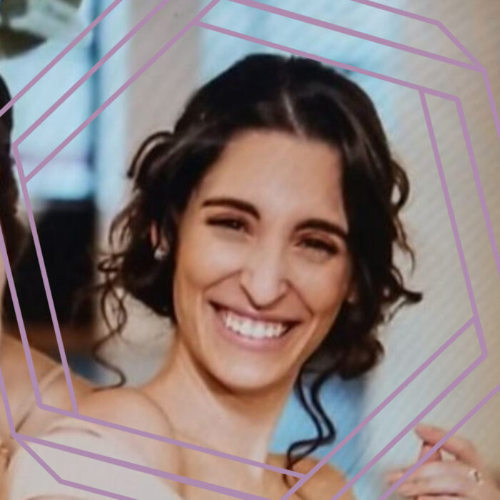 Adriana, a woman in her 20s with dark brown hair in a curled formal style, smiles at the camera. There is a stylized purple hexagon framing the photo.