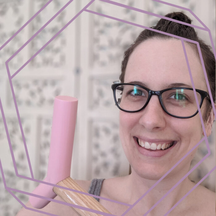 Brianne, a white woman in her 30s wearing black framed glasses and brown hair in a messy bun, smiles at the camera. She is holding the pink epoxy handle of her blonde wood cane up beside her face. There is a stylized purple hexagon framing the photo.