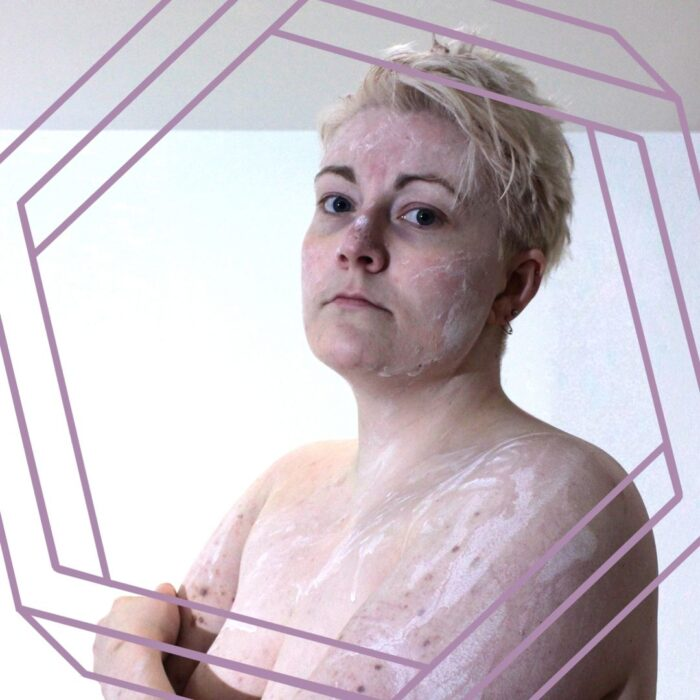 Alex, a white person with short platinum hair, turned to the side with their arms crossed, and looking seriously at the camera, in front of a plain white wall. There are streaks and splatters of white calamine lotion all over their torso so they look as if they've been lightly coated in plaster. The photo is framed by a stylized purple hexagon.
